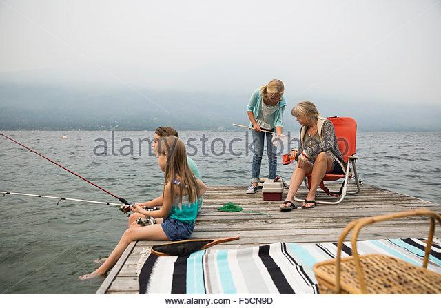 Grandmother and grandchildren fishing on lake dock - Stock Image