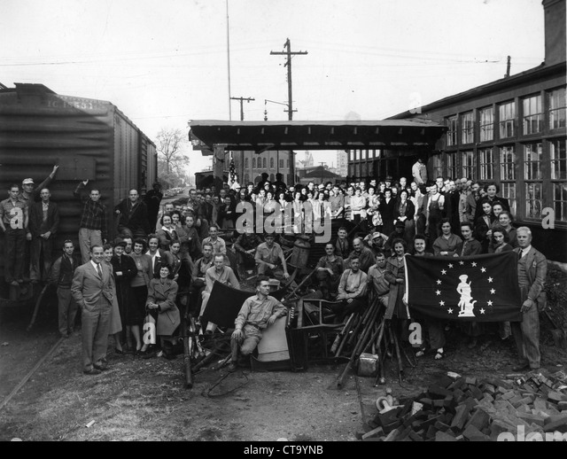 Townsfolk gathered up for group portrait during WWII national guard flag rail car small town - Stock Image