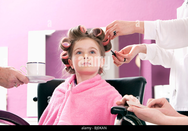 portrait of young girl at hair salon being served - Stock Image