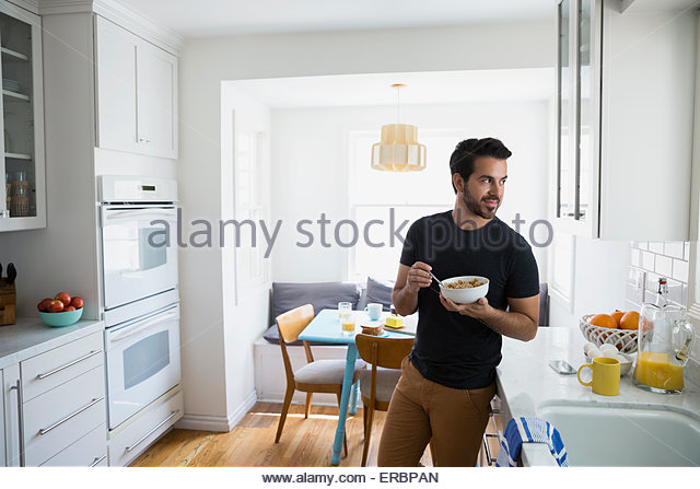 Man eating cereal and looking away in kitchen - Stock Image