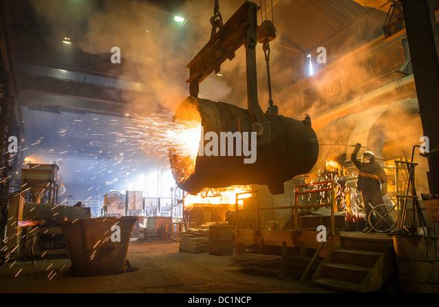 Steel worker and bucket of molten metal in steel foundry - Stock Image