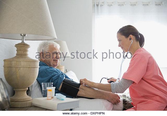 Home care nurse taking senior mans blood pressure - Stock Image