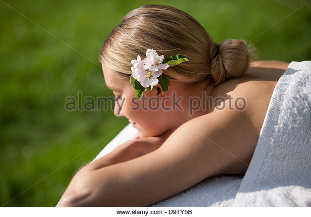A young woman laying on a massage table with apple blossom in her hair, eyes closed - Stock Image