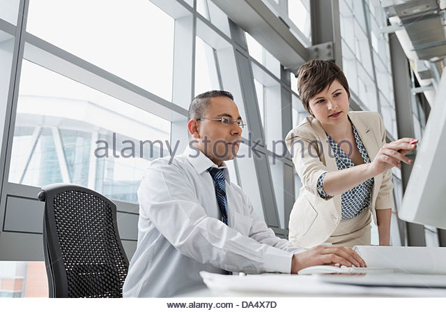 Businesswoman pointing to project on computer monitor in office building - Stock Image