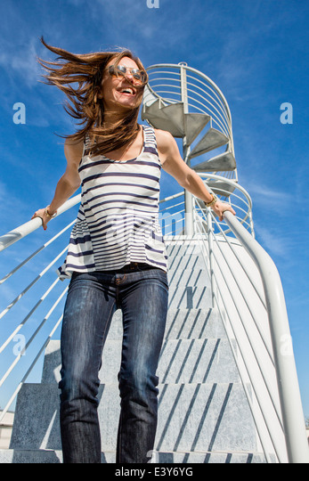 Candid portrait of mid adult woman on spiral staircase - Stock Image