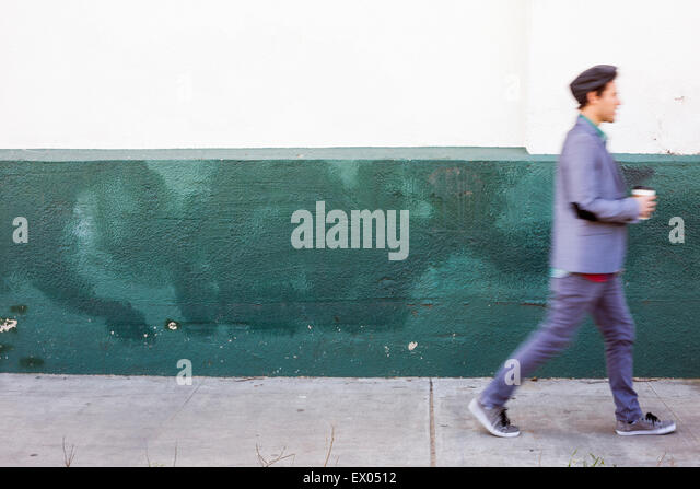Young man walking past wall - Stock-Bilder