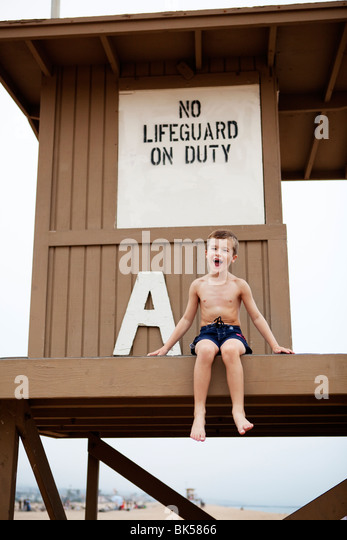 Young boy sitting on the life guard tower - Stock Image