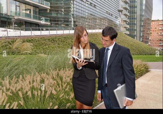 Two adults having discussion, looking at notebook - Stock Image