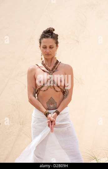 Body temple. Sensual woman in front of a natural sand dune wall holding her hands in yoga mudra. - Stock Image