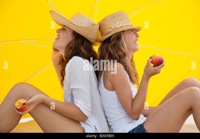 Happy friends eating fruit in the shade - Stock Image