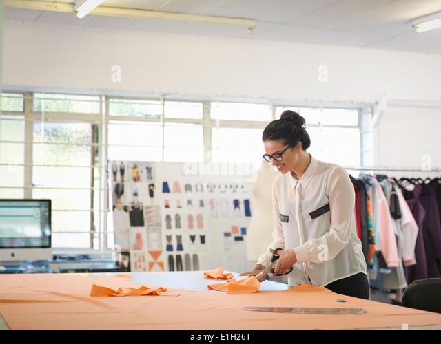 Fashion designer cutting cloth in fashion design studio - Stock Image