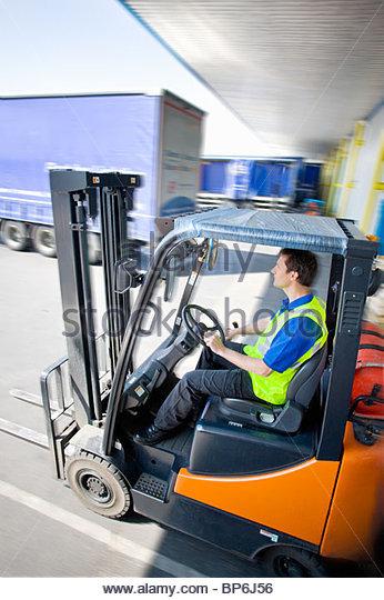 Worker driving forklift on loading dock - Stock Image