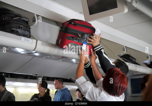 Chicago Illinois O'Hare International Airport ORD onboard United commercial airliner cabin man woman overhead - Stock Image