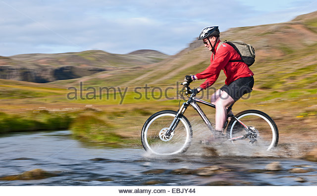 Young male mountain biker speed cycling through hot river, Reykjadalur valley, South West Iceland - Stock Image