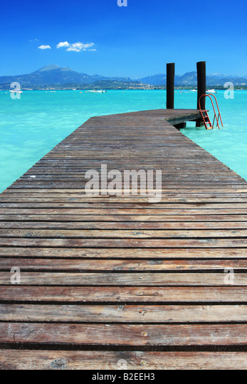 A small jetty on lake Garda Italy fantastic color in the sky and water Perfect for any sort of vacation concept - Stock Image