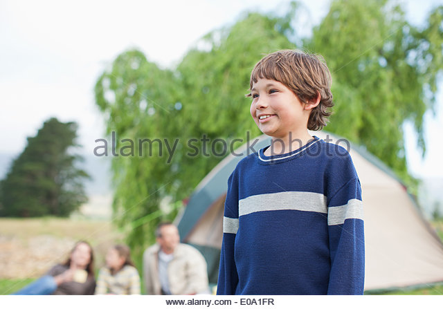 Boy standing near family camping trip - Stock Image