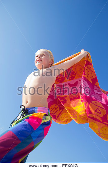 Portrait of boy holding towel above head in the wind on sunny beach - Stock Image
