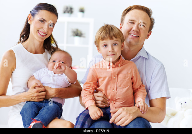 Portrait of happy family with cute sons looking at camera - Stock Image