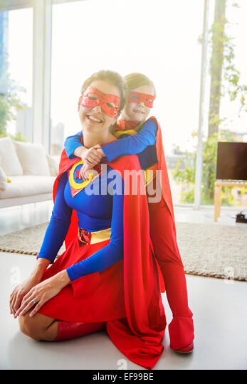 Superhero mother and son smiling in living room - Stock Image
