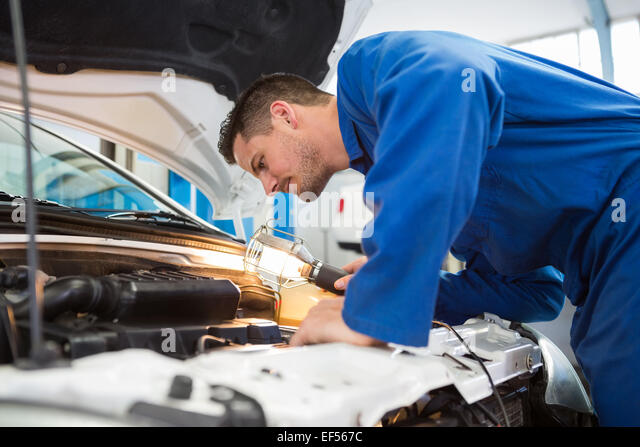 Mechanic examining under hood of car with torch - Stock-Bilder