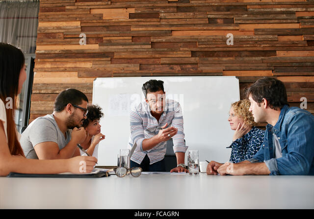 Brainstorming in a boardroom of creative office . Young creative people sitting at the table and discussing new - Stock Image