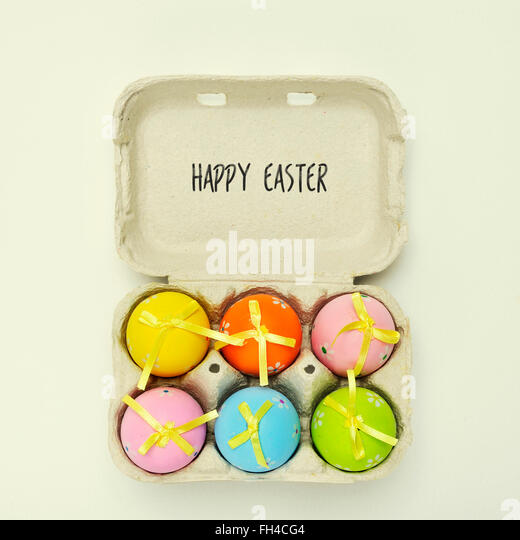 high-angle shot of an egg carton full of decorated easter eggs of different colors and the text happy easter written - Stock-Bilder