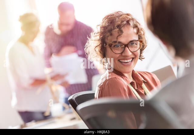 Smiling businesswoman listening to colleague in office - Stock-Bilder