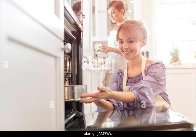 Smiling woman baking, placing cake in oven - Stock-Bilder