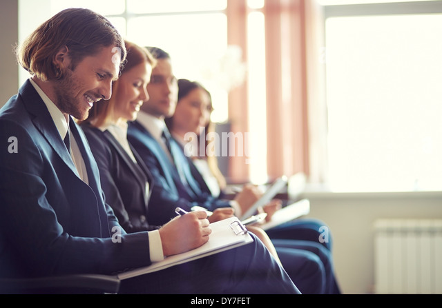 Row of business people making notes at seminar with young man on foreground - Stock Image