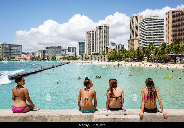 Hawaii Hawaiian Honolulu Waikiki Beach Kuhio Beach Park Pacific Ocean Hyatt Regency hotel waterfront sunbathers - Stock Image