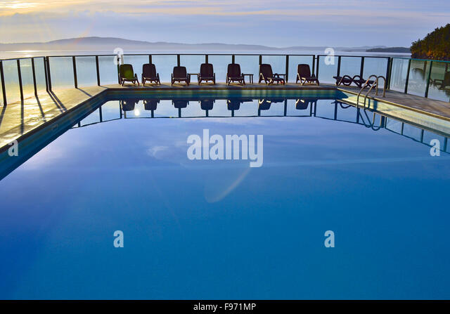 A horizontal image of an outdoor swimming pool with a line of chairs at a vacation resort on Vancouver Island B.C. - Stock-Bilder