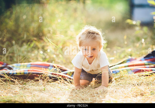 little girl crawling on the lawn - Stock Image
