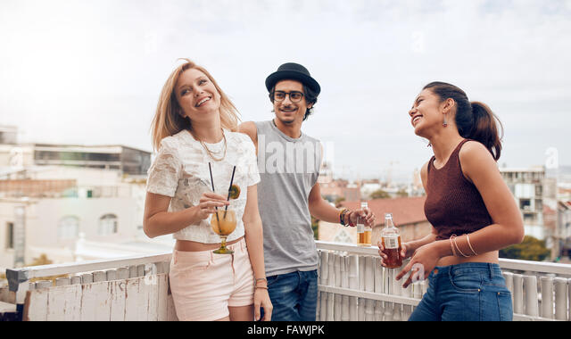 Group of happy young people standing together with drinks. Mixed race friends having rooftop party. - Stock Image