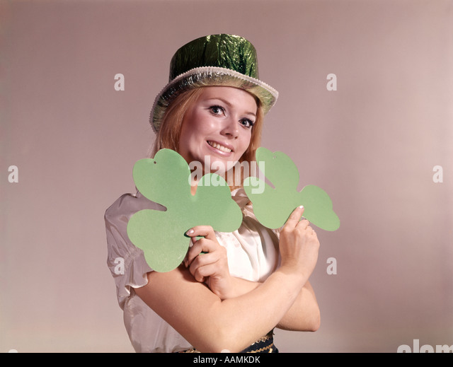 1960s 1970s RETRO IRISH WOMAN SMILING HOLDING GREEN SHAMROCKS AND WEARING GREEN PARTY HAT - Stock Image