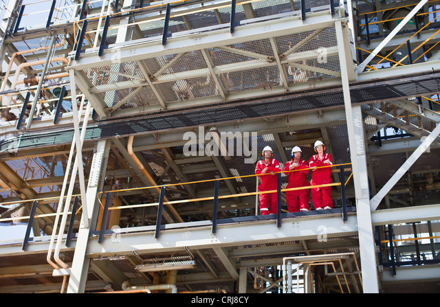 Workers standing on ledge together - Stock Image