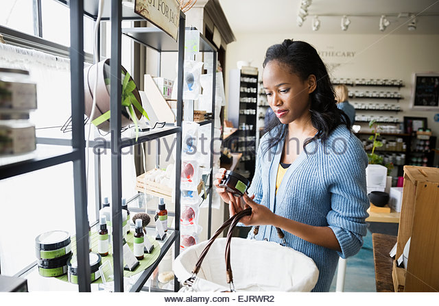 Woman reading box label in apothecary shop - Stock Image