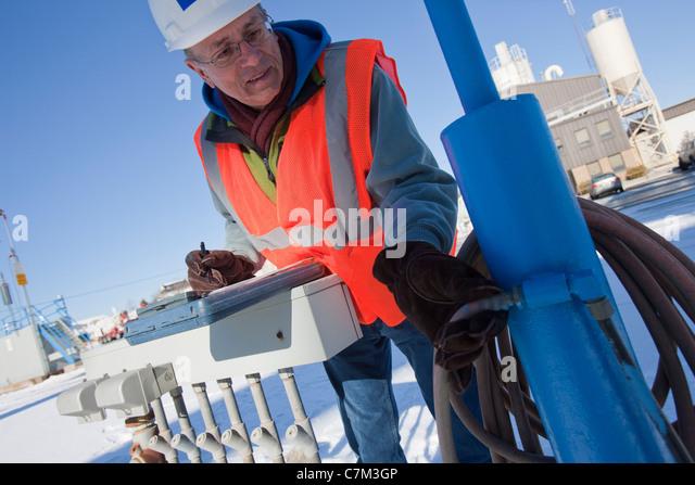 Engineer examining pneumatic hoses - Stock Image