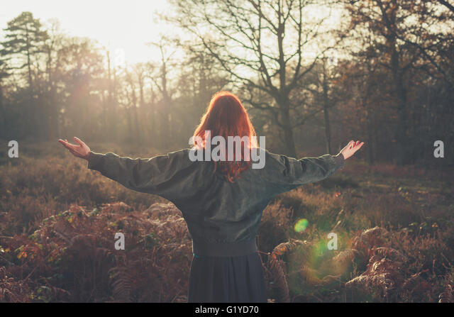 A young woman is raising her arms in joy as she is standing in a forest at sunset - Stock Image