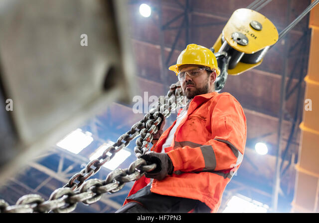 Steel worker holding crane chain in factory - Stock Image