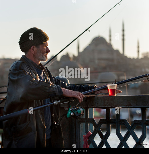 Man fishing in a river with Rustem Pasha Mosque in the background, Bosphorus River, Istanbul, Turkey - Stock Image