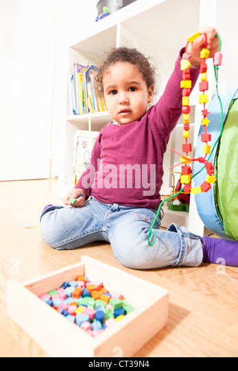 Girl playing with string of wooden beads - Stock Image