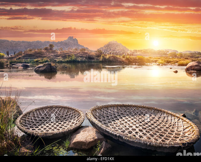 Round shape boats on Tungabhadra river at sunset sky in Hampi, Karnataka, India - Stock Image