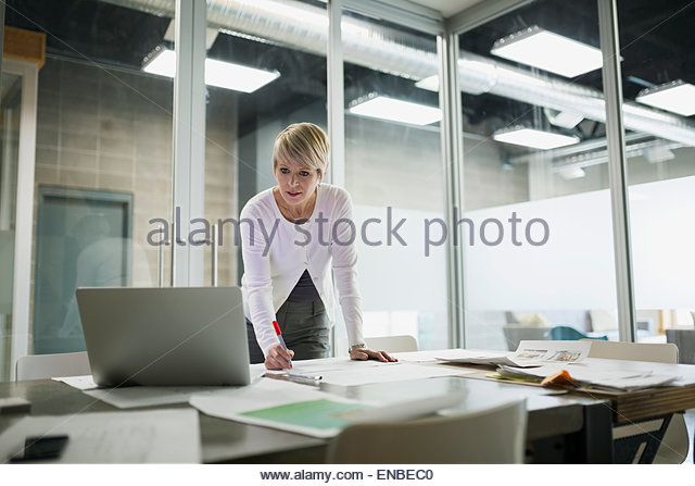 Businesswoman editing proofs at laptop in conference room - Stock Image