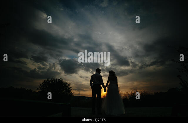 Silhouette of  wedding couple in field - Stock-Bilder
