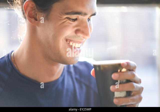 Young man holding coffee cup, indoors - Stock Image