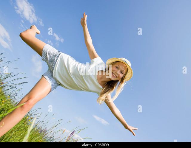 Austria, Teenage girl doing gymnastics in field, smiling, portrait - Stock Image