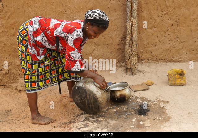 Woman scrubbing pot in Mognori Eco-Village, Ghana - Stock Image