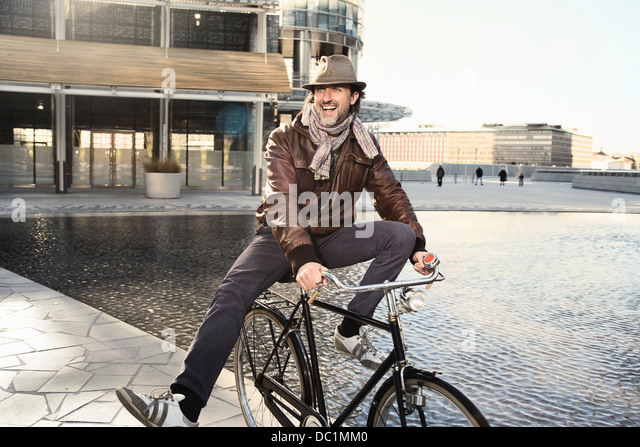 Mid adult man enjoying bike ride in city - Stock Image