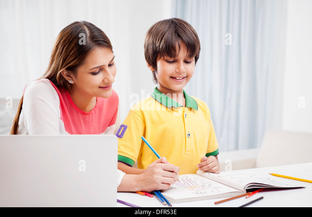 Woman assisting her son in drawing - Stock Image