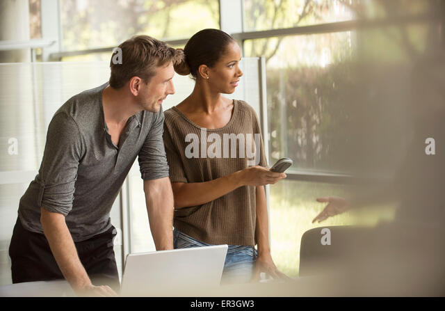 Office workers cooperating on assignment - Stock Image